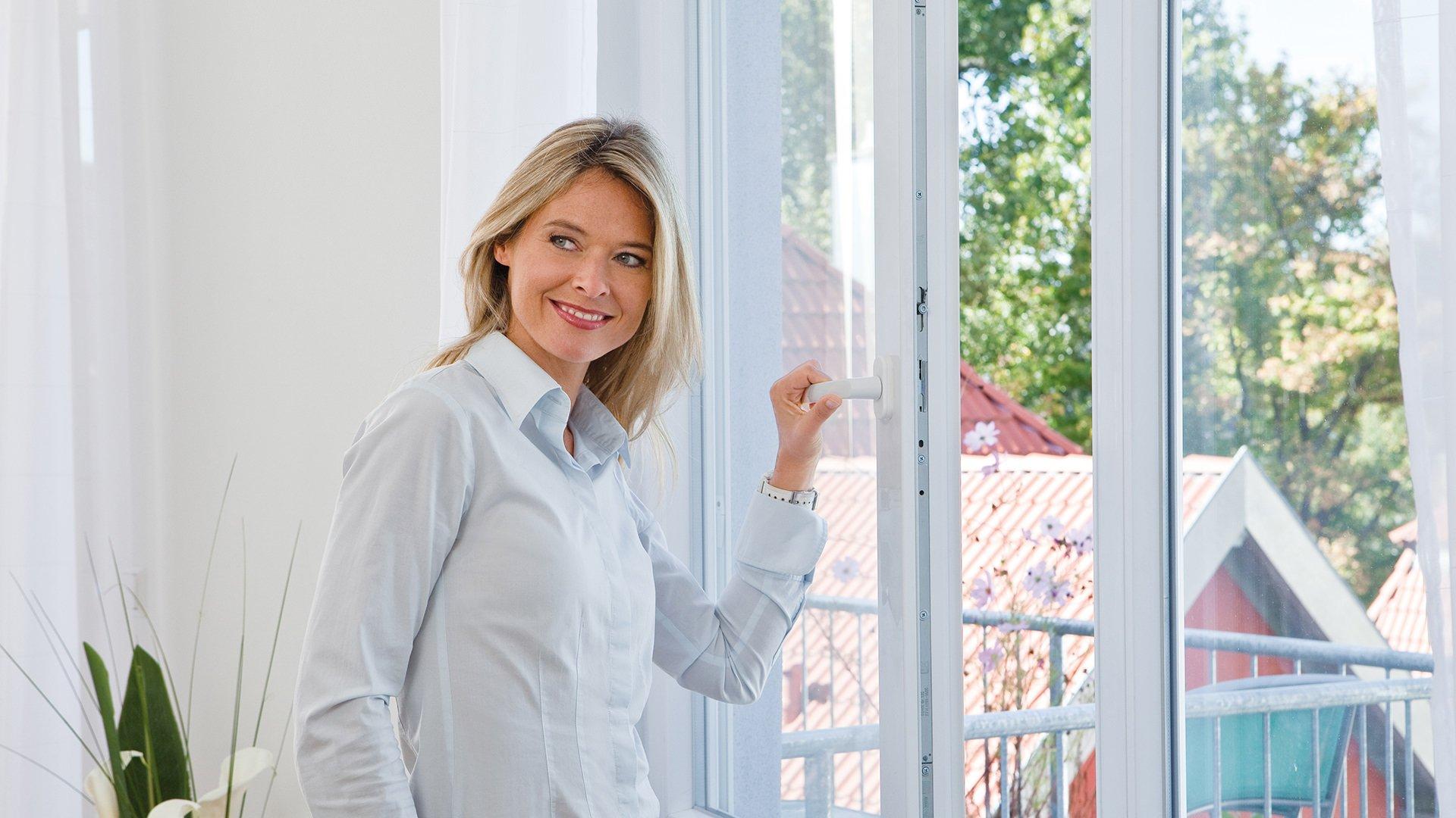 Frau öffnet ein Fenster mit Fliegengitter