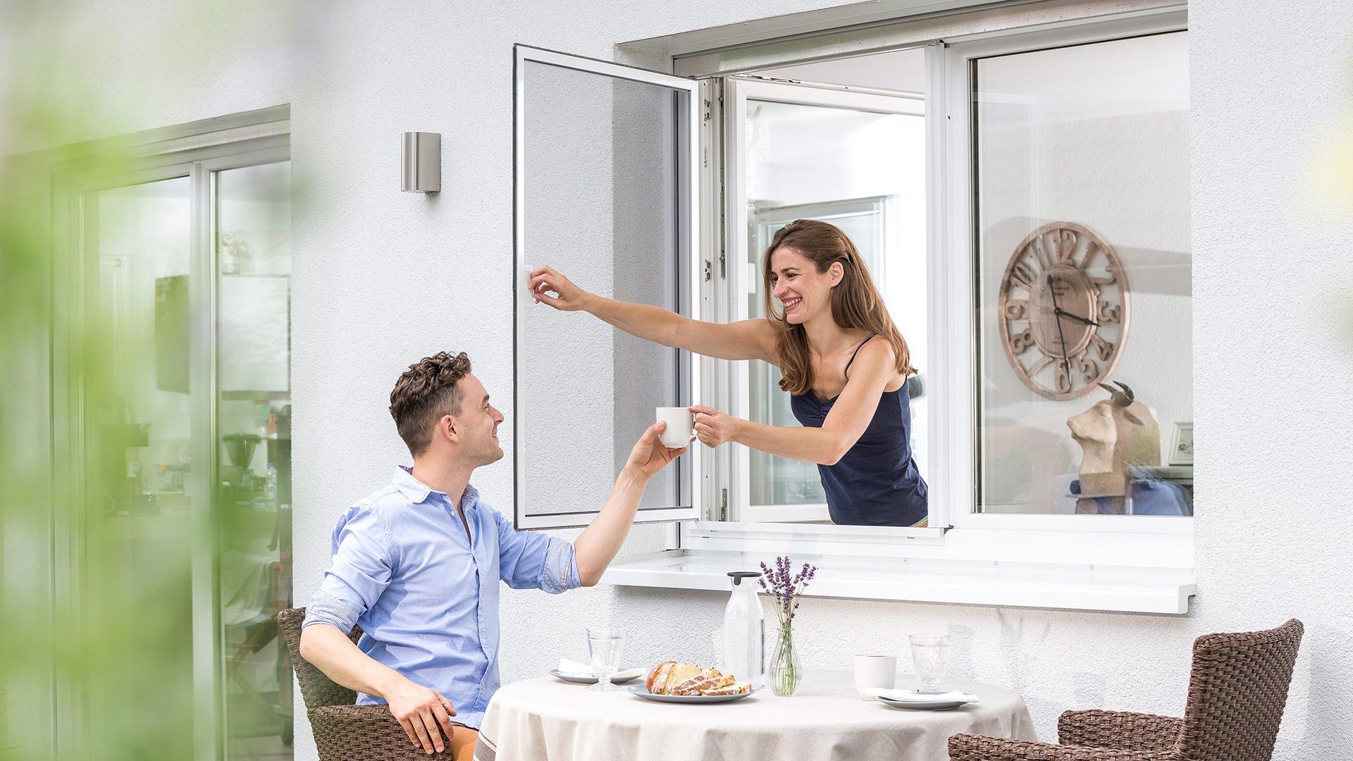 Eine Frau öffnet ein Fliegengitter-Rahmen und reicht einem Mann einen Kaffee