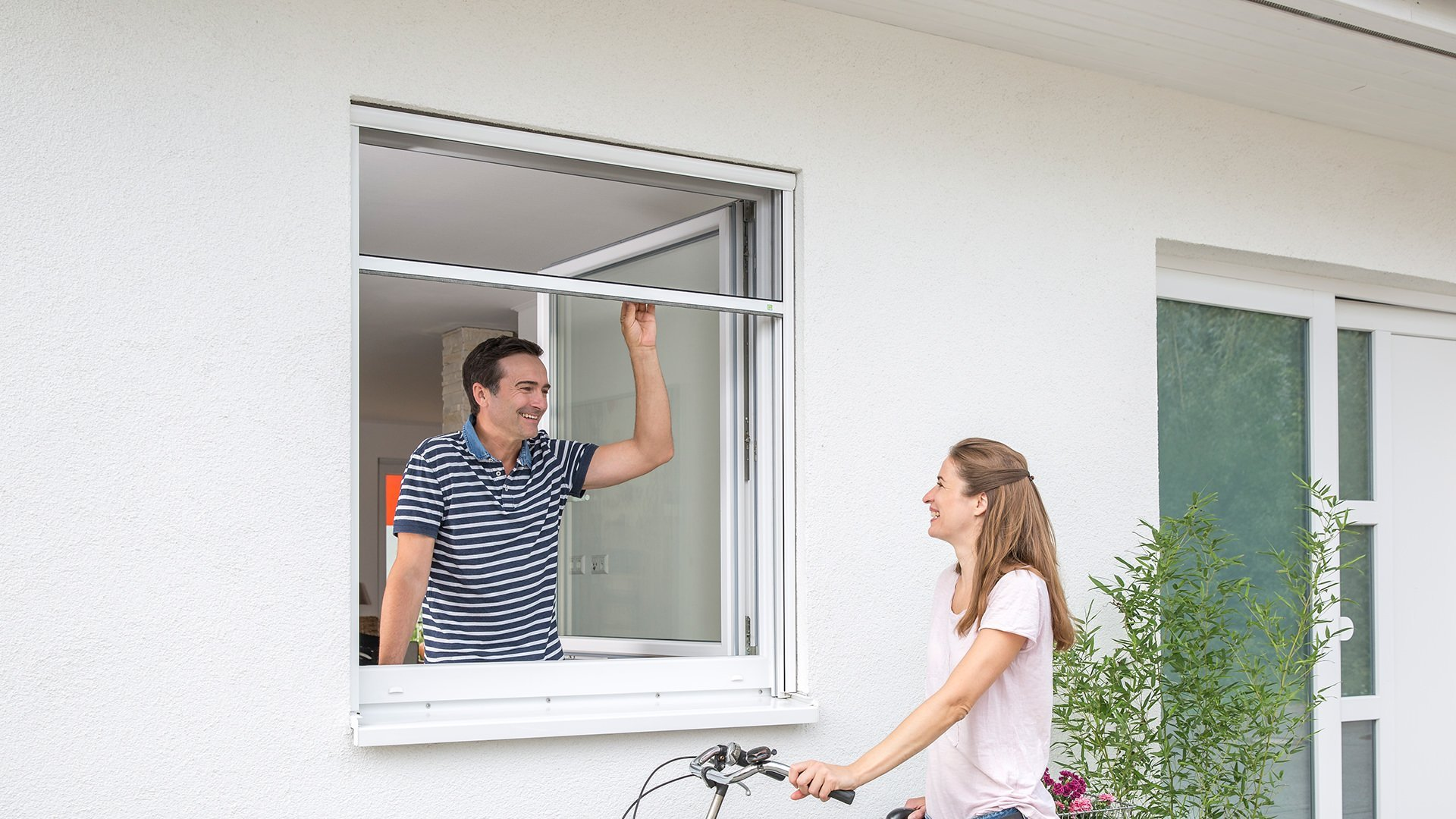 Ein Mann unterhält sich aus einem Fenster mit Fliegengitter-Rollo mit einer Frau