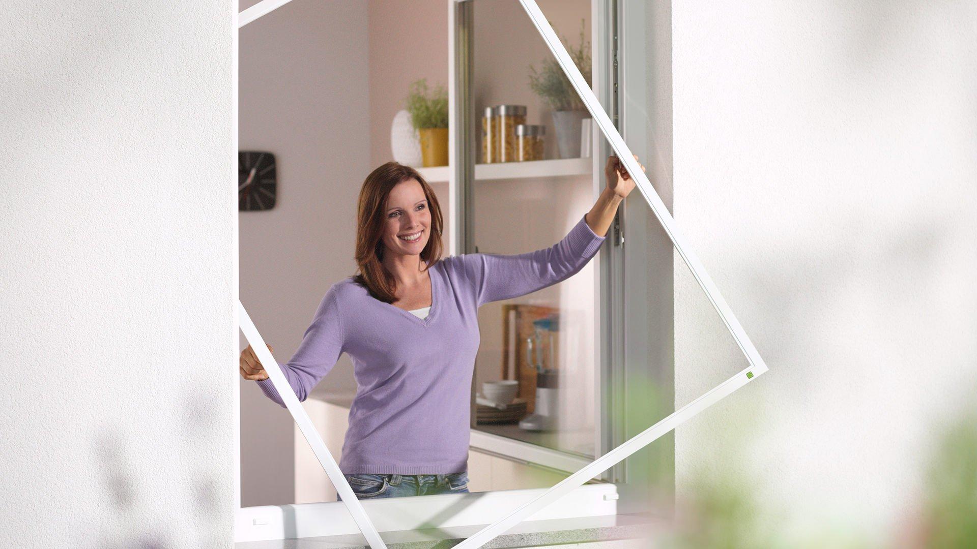 Ein Frau bringt ein Fliegngitter-Spannrahmen an ein Fenster an