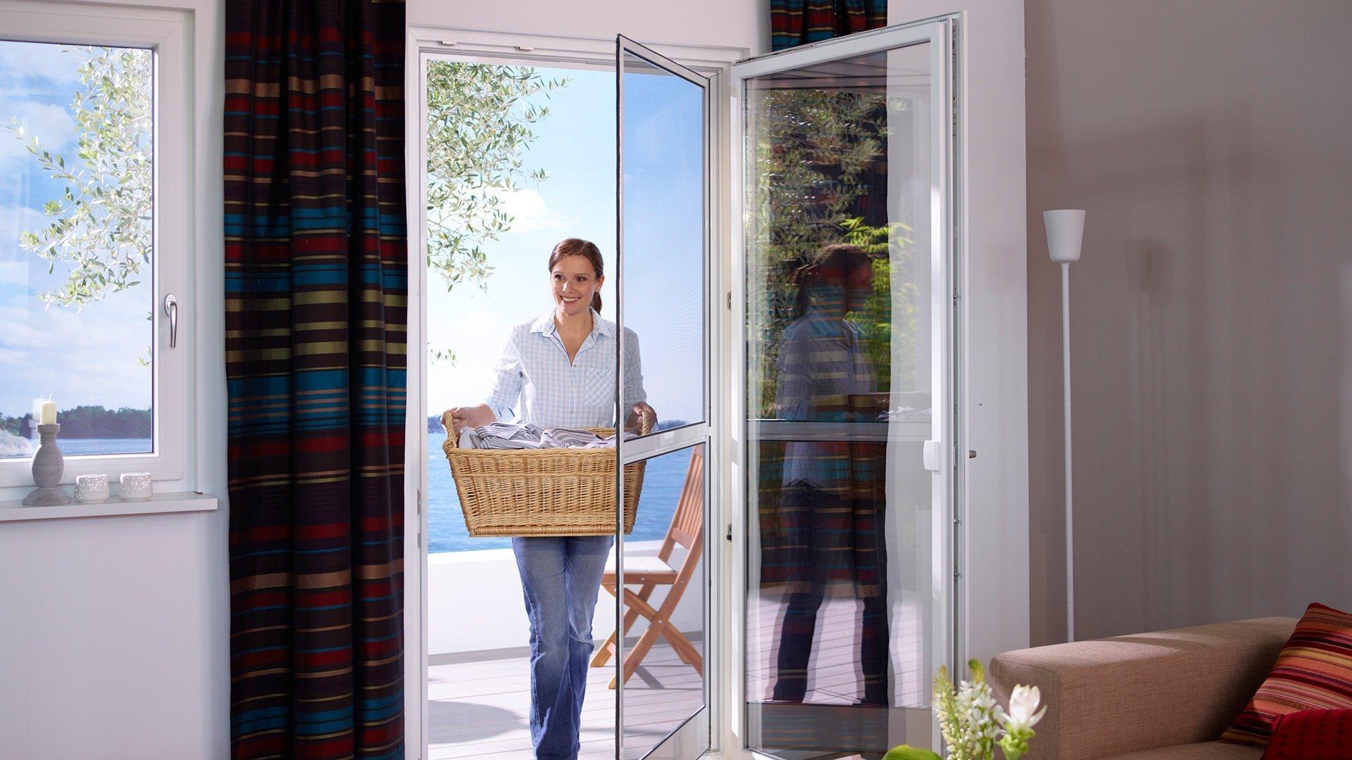 Eine Frau bringt einen Korb Wäsche durch eine Fliegengitter-Pendeltür ins Haus
