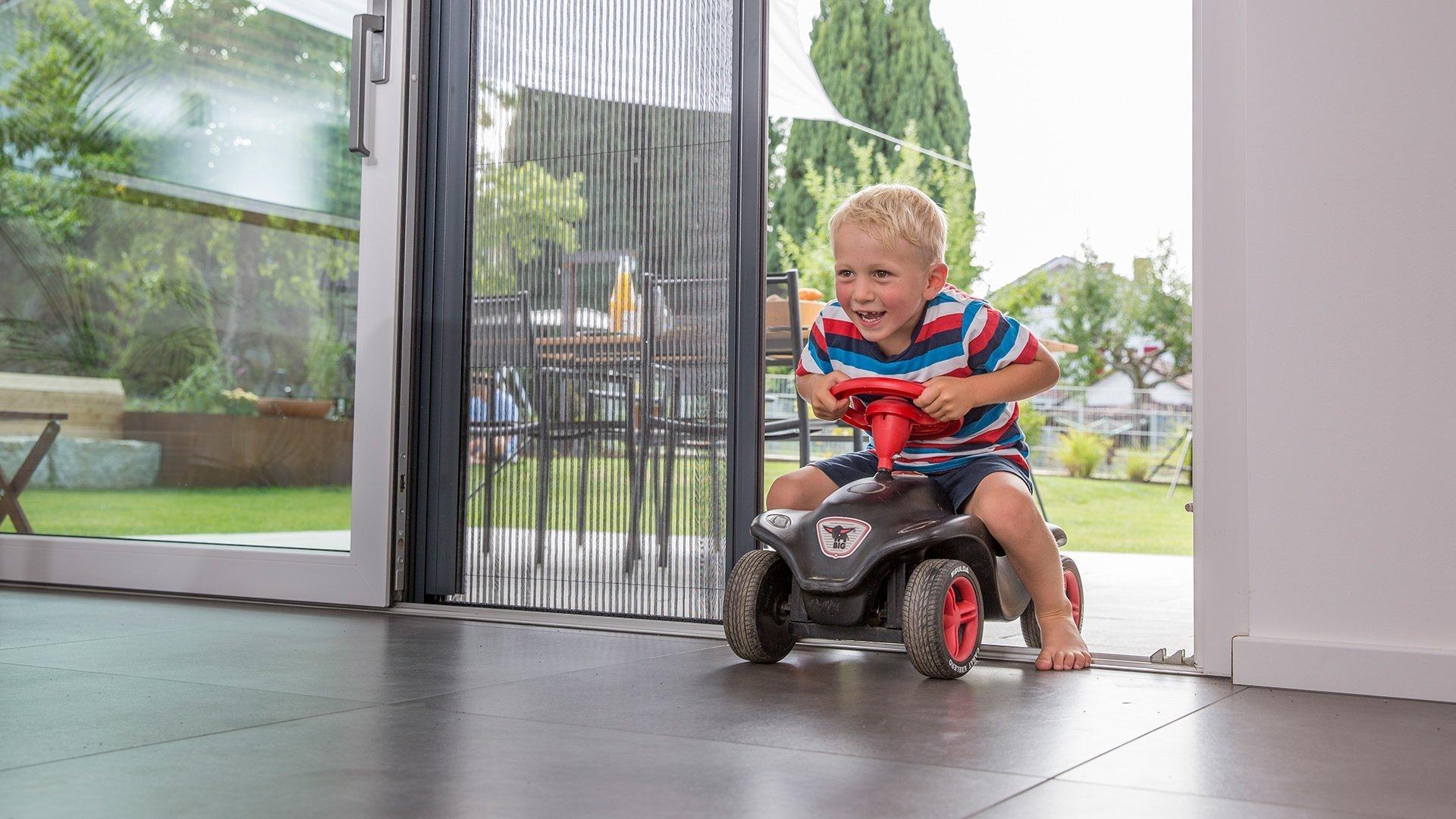 Ein junge fährt auf einem Spielauto von der Terrasse ins Haus