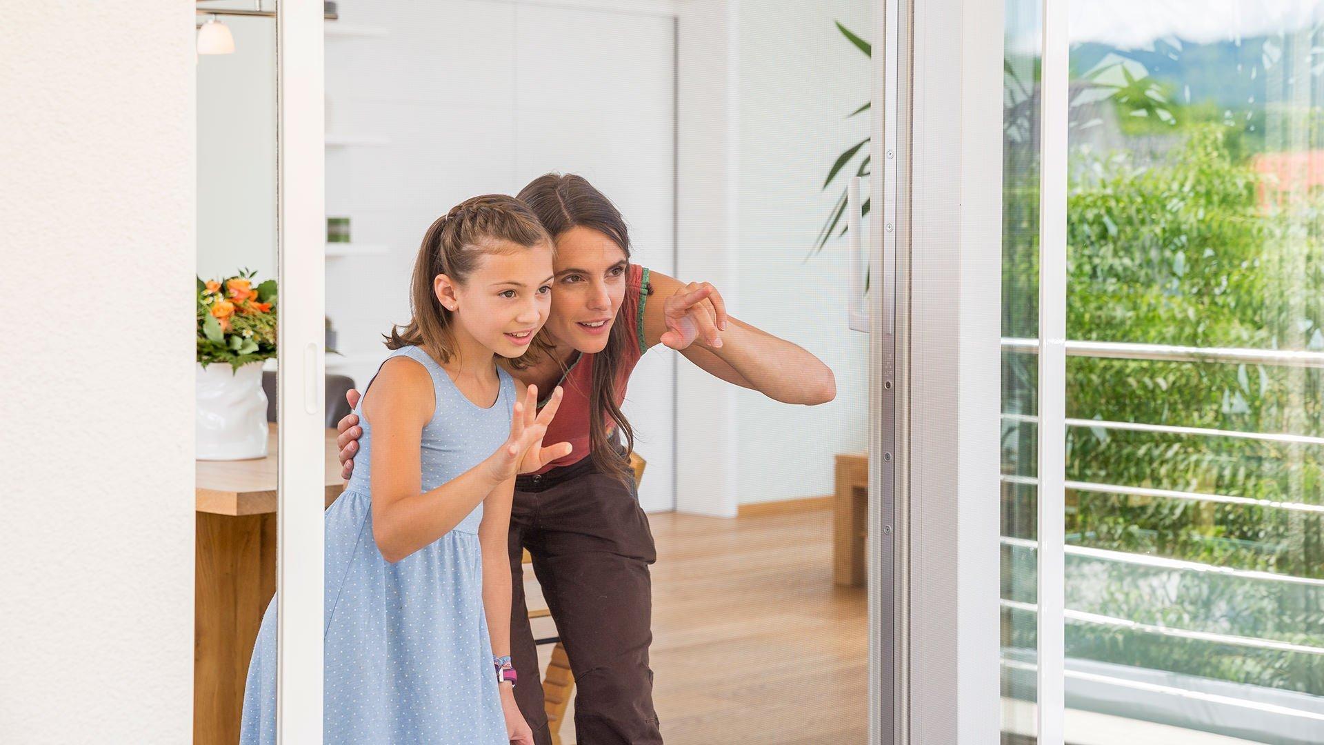Mutter und Tochter betrachten eine Schiebeanlage mit Insektenschutz
