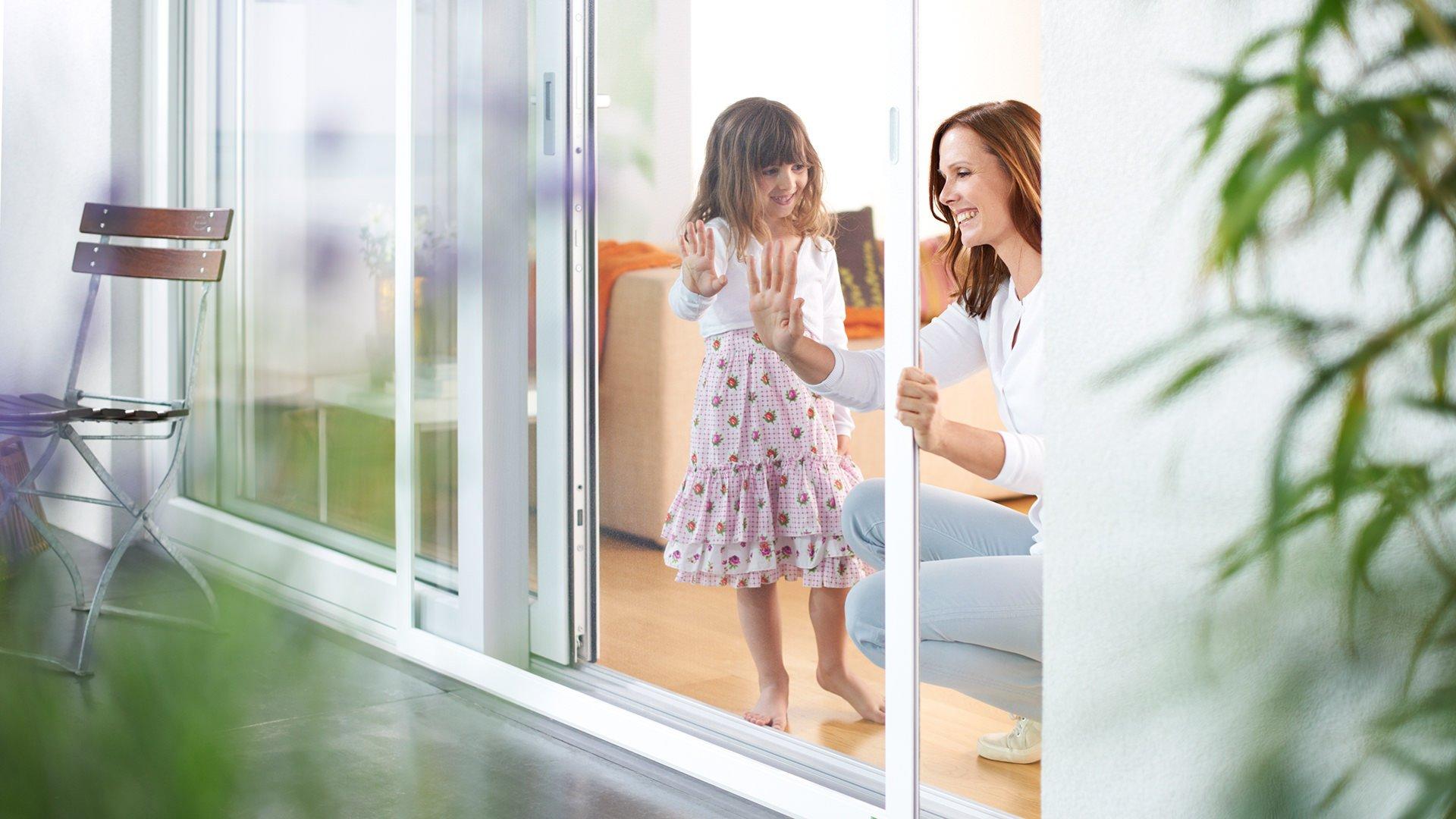 Frau und kleines Mädchen schauen sich ein Fliegengitter an der Terrasentür an