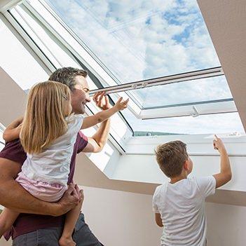 Ein Vater mit 2 Kindern schaut aus einem Dachfenster