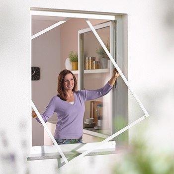 Frau mit einem Fliegengitter-Spannrahmen an einem Fenster