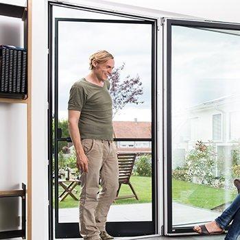 Mann kommt durch eine Fliegengitter-Tür ins Haus