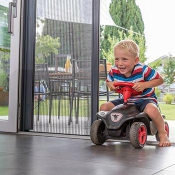 Ein Jung fährt mit einem Bobby-Car von der Terrasse ins Haus