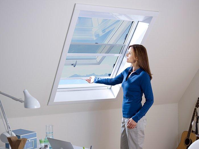 Frau bedient Fliegengitter mit Sonnenschutzgewebe an einem Dachfenster