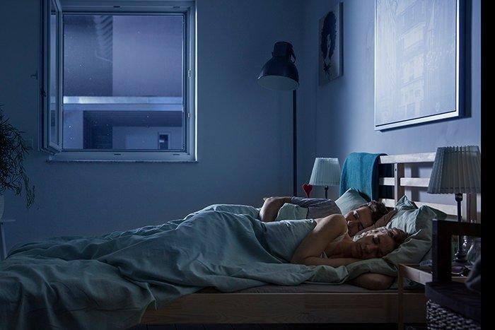 Paar liegt bei offenem Fenster im Bett und schläft