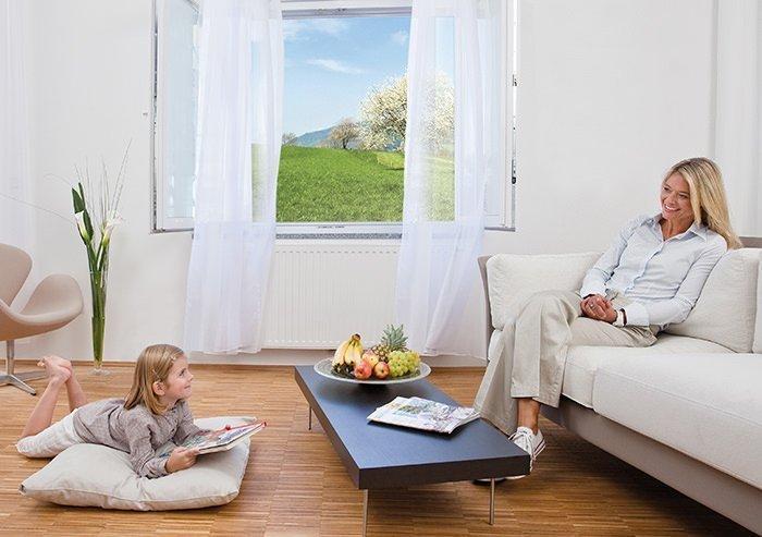 Mutter und Tochter sitzen im Wohnzimmer bei geöffnetem Fenster
