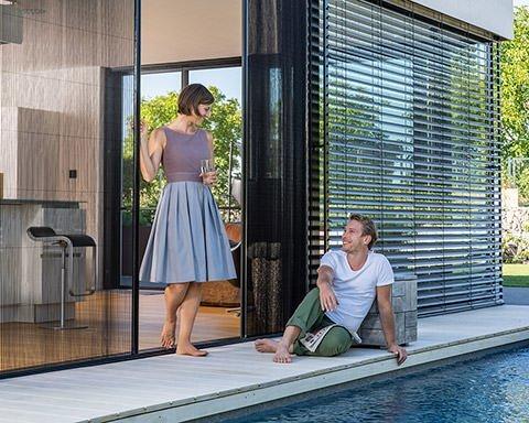 Ein junges paar unterhält sich auf der Terrasse. Er sitzt auf dem Boden am Pool, sie lehnt sich an ein Fliegengitter-Plissee