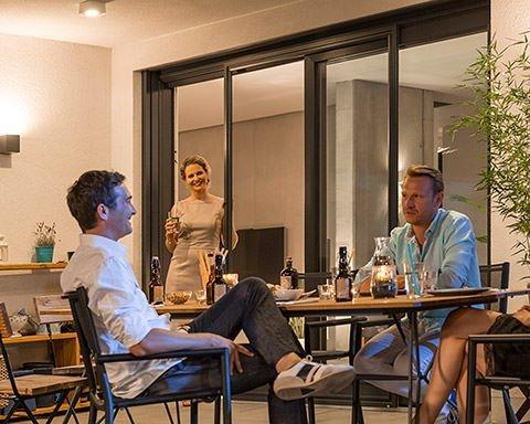 Gäste sind an einem Tisch auf der Terrasse im Gespräch, während die Gastgeberin an einer Gligengitter-Schiebetür gelehnt zusieht.