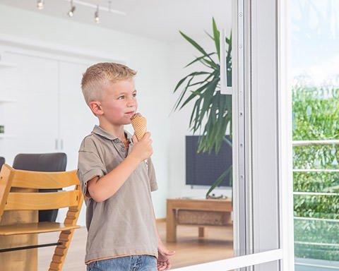 Ein Junge mit einem Eis in der Hand schaut durch das Gewebe einer Fliegengitter-Schiebetür in den Garten
