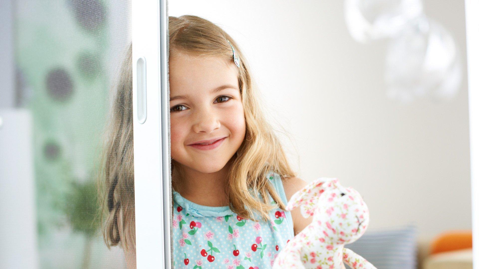 Ein Mädchen mit Stofftier lehnt an einer Fliegngitter-Schiebetür