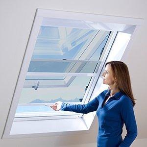 Frau steht an einem Dachfenster und bedient einen Schieberahmen