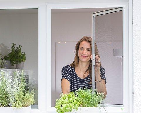 Frau öffnet Fliegengitter-Fenster und schaut aus der Küche