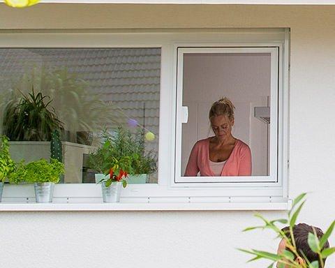 Frau steht vor einem Küchenfenster mit Fliegengitter-Rahmen