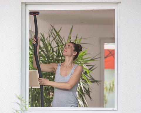 Frau reinigt Fliegengitter mit einem Staubsauger
