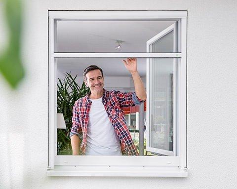 Eine Mann schaut aus einem Fenster mit halb geschlossenem Fliegengitter-Rollo