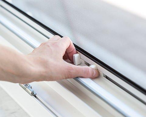 Eine hand betätigt die Schließmechanik eines Fliegengitter-Rollos für Fenster