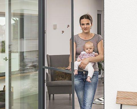 Frau mit Baby auf dem Arm geht durch eine Fliegengittertür