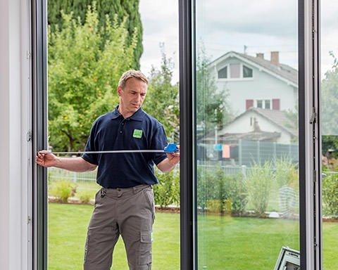 Monteur mißt die Breite einer Terrassentür mit einem Maßband